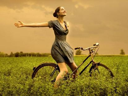 chica feliz sonriendo en bicicleta